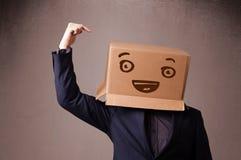 打手势与在他的头的一个纸板箱的年轻人有面带笑容的 免版税库存图片