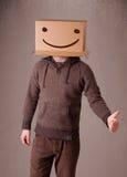 打手势与在他的头的一个纸板箱的年轻人有面带笑容的 图库摄影