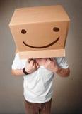 打手势与在他的头的一个纸板箱的年轻人有面带笑容的 免版税图库摄影