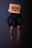 打手势与在他的头的一个纸板箱的年轻人有面带笑容的 免版税库存照片