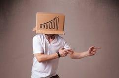 打手势与在他的头的一个纸板箱的年轻人有diagra的 库存图片