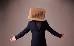 打手势与在他的头的一个纸板箱的年轻人有diagra的 图库摄影