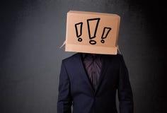 打手势与在他的头的一个纸板箱的年轻人有exclam的 免版税库存图片