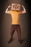 打手势与在他的头的一个纸板箱的年轻人有exclam的 免版税库存照片