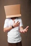 打手势与在他的头的一个纸板箱的年轻人 免版税库存照片