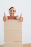 打手势与堆的妇女赞许箱子在一个新房里 免版税库存图片