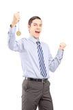 打手势与奖牌的激动的年轻专业人幸福 免版税库存图片