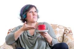 打手势到咖啡的做鬼脸的妇女 库存照片