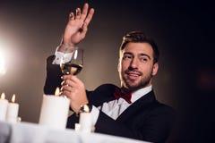 打手势和拿着杯酒的beardman在餐馆 免版税库存照片