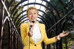 打手势唱歌入话筒的女商人 免版税库存图片
