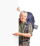 打手势在一个空白面板的一个成熟背包徒步旅行者 库存图片