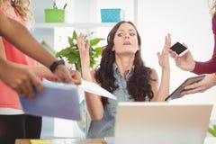 打手势在书桌的沮丧的女实业家 免版税图库摄影
