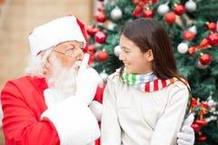 打手势在嘴唇的圣诞老人手指在女孩 免版税库存照片
