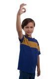 打手势好手标志的逗人喜爱的男孩 免版税库存照片