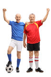 打手势幸福的两位年长足球运动员全长画象  库存照片