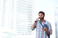 打手势微笑的人,当使用手机在城市时 图库摄影