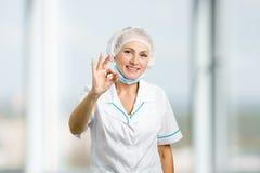 打手势微笑的女性的外科医生好 库存图片