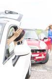 打手势恼怒的妇女,当谈话与在路时的女性失事的汽车 免版税库存图片