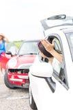 打手势恼怒的妇女,当谈话与在路时的女性失事的汽车 库存图片