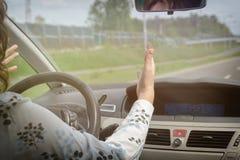 打手势恼怒的妇女,当驾驶汽车时 图库摄影