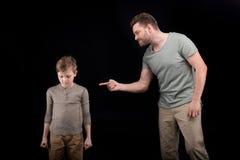 打手势恼怒的父亲威胁和惊吓了小儿子 免版税库存图片