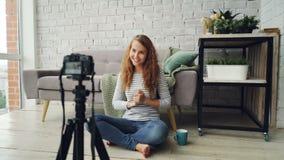 打手势愉快的女性的博客作者记录互联网videolog的录影谈话和显示翘拇指和摇手 影视素材