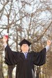 打手势成功的成熟大学毕业生在公园 免版税库存照片
