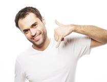 打手势手机的人在他的面孔附近 免版税库存图片