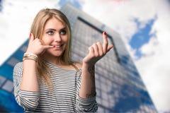 打手势手机的美丽的年轻微笑的妇女在耳朵附近 免版税图库摄影