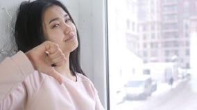 打手势拇指的生气年轻亚裔妇女下来,室内 影视素材