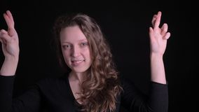 打手势横渡手指的年轻卷发的女孩画象显示愉快的希望入在黑背景的照相机 股票录像
