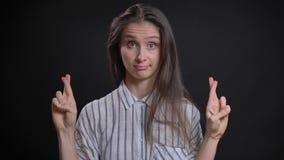 打手势横渡手指的美丽的白种人长发妇女画象签字显示对运气的希望在黑色 股票录像