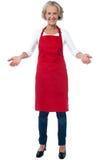 打手势欢迎的愉快的年迈的厨师 免版税库存照片