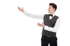 打手势欢迎的年轻微笑的侍者或男管家-隔绝在w 免版税库存照片