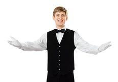打手势欢迎的年轻愉快的微笑的侍者 免版税库存图片