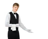打手势欢迎的年轻英俊的侍者 免版税库存照片
