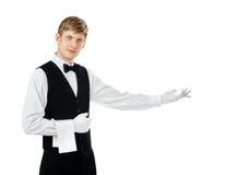 打手势欢迎的年轻英俊的侍者 免版税库存图片