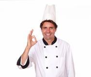 打手势正号的吸引人男性厨师 免版税图库摄影
