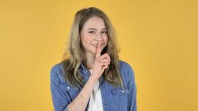 打手势沈默,在嘴唇的手指,黄色背景的年轻俏丽的女孩 股票录像