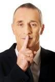 打手势沈默标志的商人画象 免版税库存图片