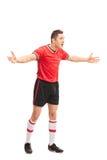 打手势用他的手的生气的足球运动员 免版税库存图片