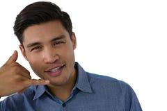打手势电话手标志的年轻商人画象 库存照片