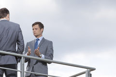 打手势的商人,当沟通与工友反对天空时 免版税库存图片