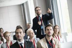 打手势的商人,当问问题在研讨会期间在会议中心时 免版税图库摄影