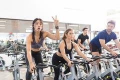 打手势胜利的妇女,当行使在健身房时的转动的自行车 免版税库存图片