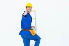 打手势赞许的安装工,当爬梯凳时 库存照片