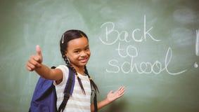 打手势赞许的小女孩在教室 免版税库存图片