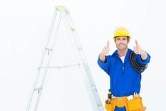 打手势赞许的愉快的电工由梯子 免版税库存图片