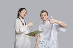 打手势赞许的愉快的医生和患者画象  免版税库存照片