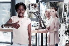 打手势超级标志的快乐的孩子在看见真正的机器人以后 免版税图库摄影